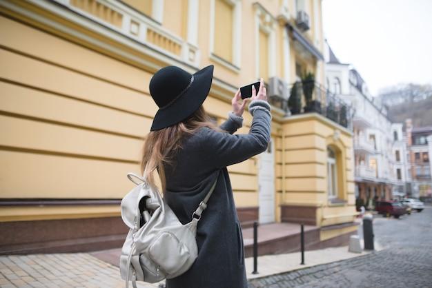 Garota elegante turista tira uma foto da cidade velha em seu próprio smartphone.