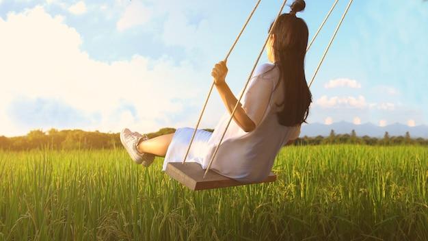 Garota em balanço na luz solar.