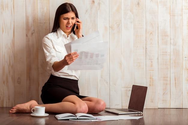 Garota em camisa branca segurando documentos e falando no telefone.