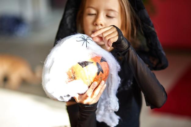Garota em casa com fantasia de halloween com abóbora jack ou laurent nas mãos, criança usando máscara preta protegendo contra coronavírus, halloween em quarentena.