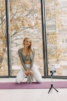 Garota em casa. mulher faz ioga. a senhora grava um videoblog.