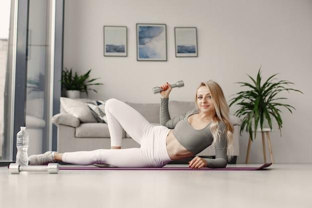 Garota em casa. mulher faz ioga. senhora com halteres e água.