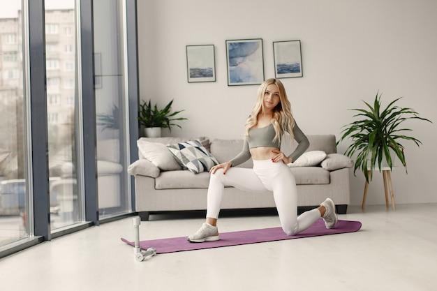 Garota em casa. mulher faz ioga. senhora com halteres.