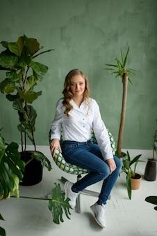 Garota em casa, na cozinha branca, com roupas verdes, sentado em uma cadeira verde com um gato nos braços