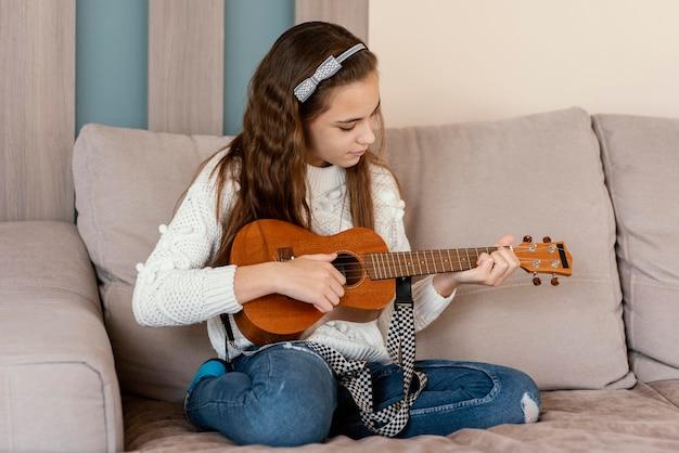 Garota em casa tocando violão