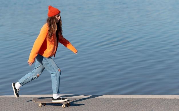 Garota em cena completa andando de skate à beira do lago