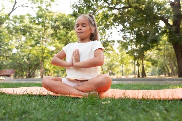 Garota em cena completa meditando ao ar livre