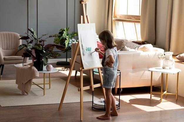Garota em cena completa pintando com pincel