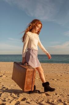 Garota em cena completa segurando mala na praia