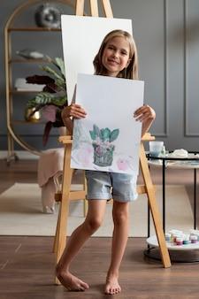 Garota em cena completa segurando uma pintura