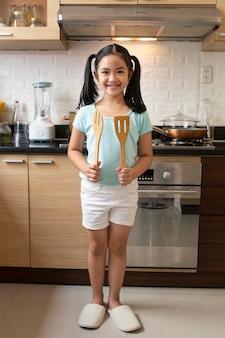Garota em cena completa segurando utensílios de cozinha