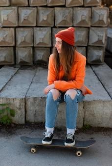 Garota em cena completa sentada com skate ao ar livre