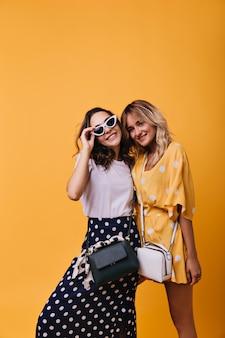 Garota em êxtase em saia longa, tocando seus óculos de sol brancos enquanto posava com a melhor amiga. retrato interno de atraentes modelos femininos dançando.