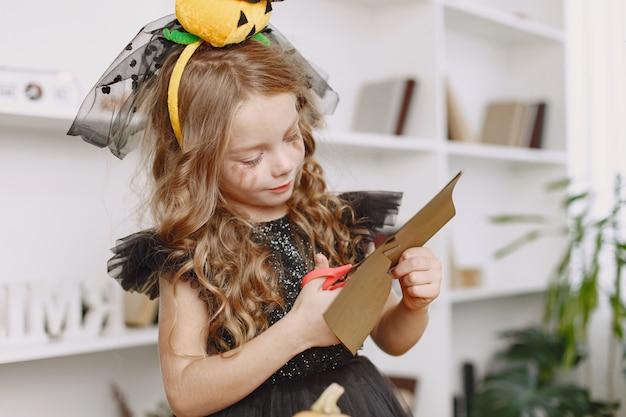 Garota em fantasias de festa fazendo artesanato em casa