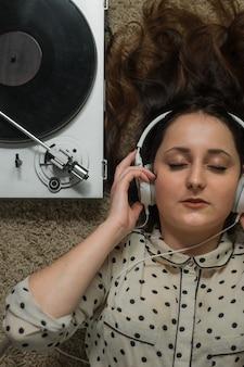 Garota em fones de ouvido brancos no chão ouvindo uma plataforma giratória.