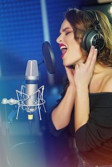 Garota em fones de ouvido cantando uma música.