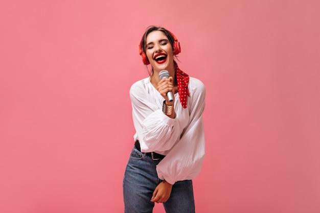 Garota em fones de ouvido segura o microfone e canta sua música favorita. jovem mulher com roupas da moda com batom brilhante posando.