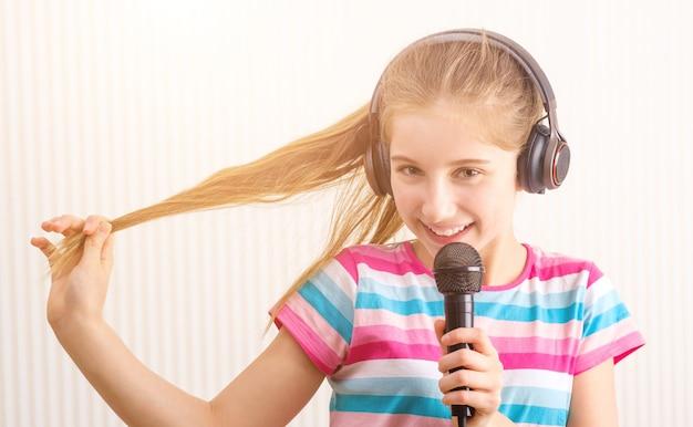 Garota em fones de ouvido segurando o microfone