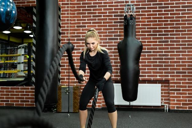 Garota em forma de jovem com roupas esportivas treina na academia