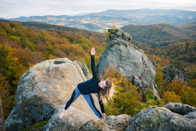 Garota em forma desportiva está praticando ioga e fazendo asana utthita trikonasana no topo da montanha