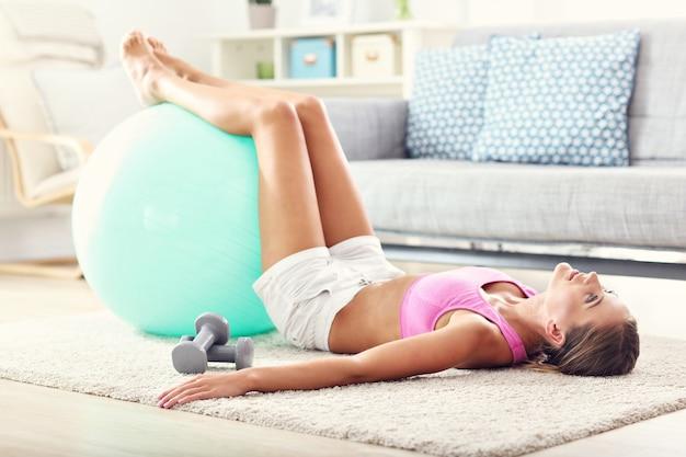 Garota em forma fazendo abdominais em casa na sala de estar