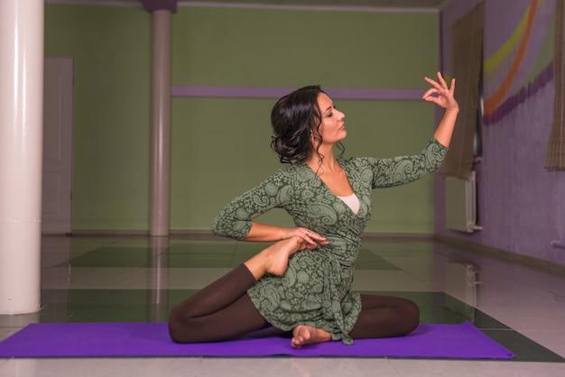 Garota em forma fazendo ioga asana em um estúdio