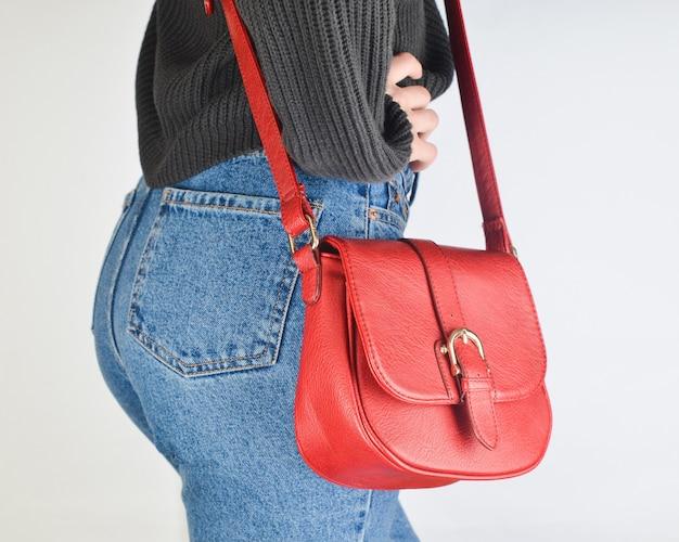 Garota em forma jeans, camisola e com saco sobre as probabilidades posando. vista lateral.