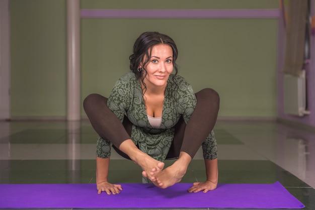 Garota em forma praticando aula de ioga em um estúdio