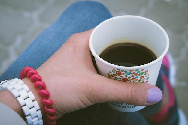 Garota em jeans azul, descansando e bebendo café ao ar livre