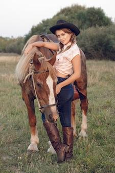 Garota em jeans de chapéu preto de cowboy com cavalo