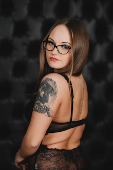 Garota em lingerie sexy preta e óculos com uma tatuagem no braço, posando em uma parede preta