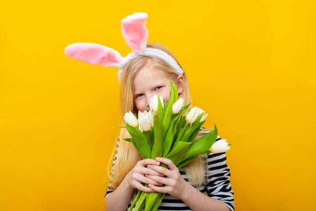 Garota em orelhas de coelho coelho na cabeça escondida atrás de tulipas buquê de flores em amarelo