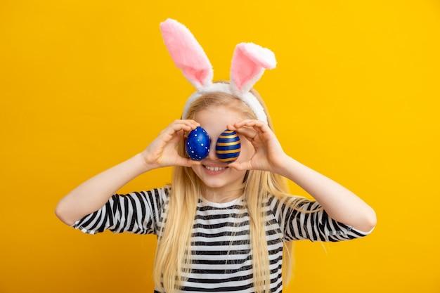 Garota em orelhas de coelho coelho na cabeça segurando ovos de páscoa nos olhos em amarelo