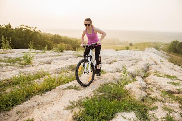 Garota em passeios de bicicleta de montanha na trilha em um belo nascer do sol.