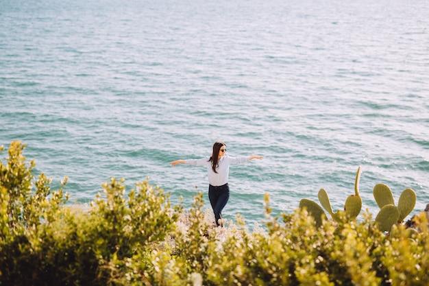 Garota em pé com as mãos para cima perto do mar