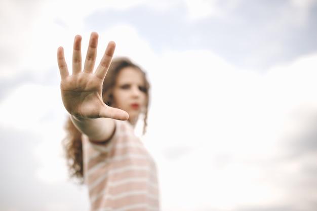 Garota em pé contra o fundo do céu nublado e mostrar mão de parada