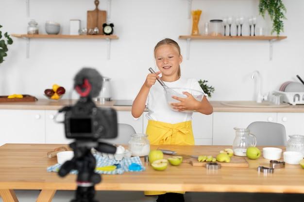 Garota em plano médio cozinhando para a câmera