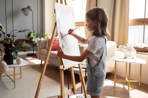 Garota em plano médio pintando em casa