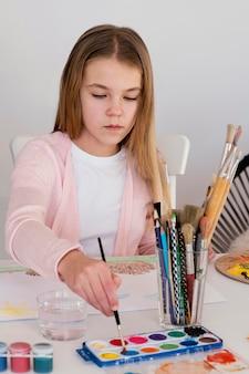 Garota em plano médio usando aquarelas