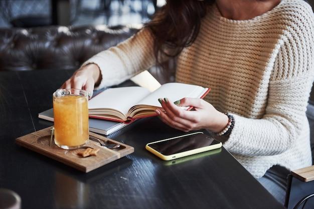 Garota em processo de estudo. cortada perto foto de mulher ler o livro no restaurante com bebida amarela e smartphone na mesa