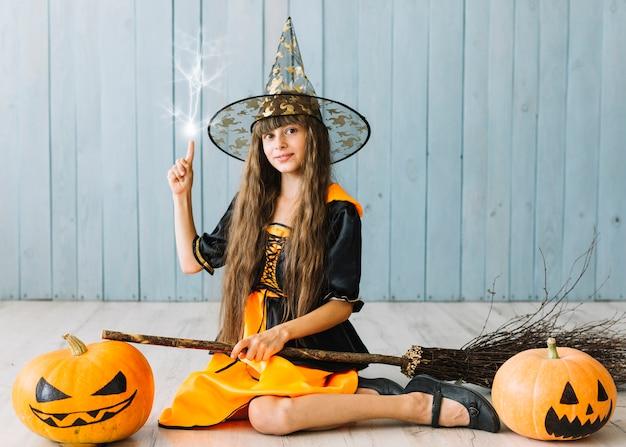 Garota em roupa de bruxa sentada no chão, fazendo mágica