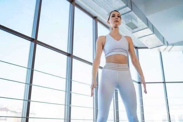 Garota em roupas esportivas em pé na sala