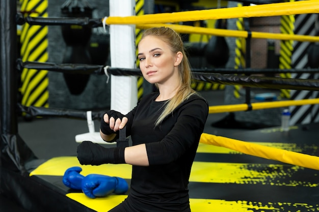 Garota em roupas esportivas usando luvas de boxe durante um treino