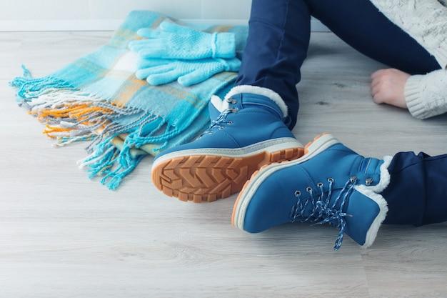 Garota em sapatos de inverno no chão
