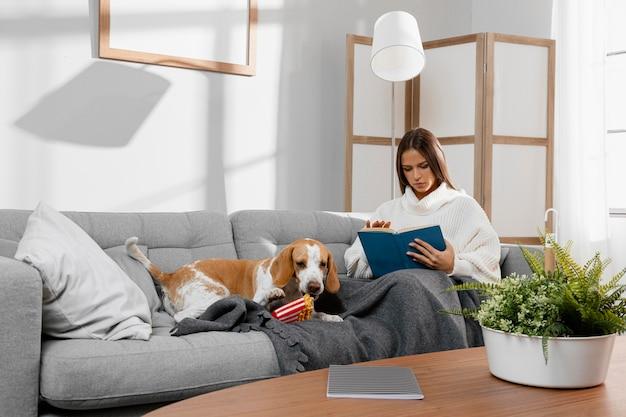 Garota em tiro completo no sofá com cachorro