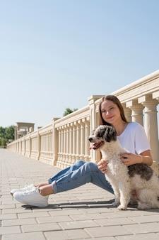 Garota em tiro completo segurando um cachorro fofo