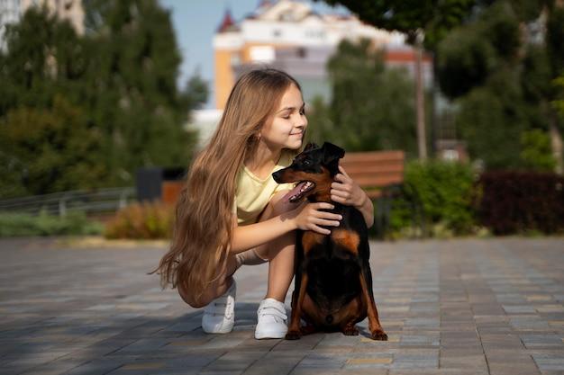 Garota em tiro completo segurando um cachorro