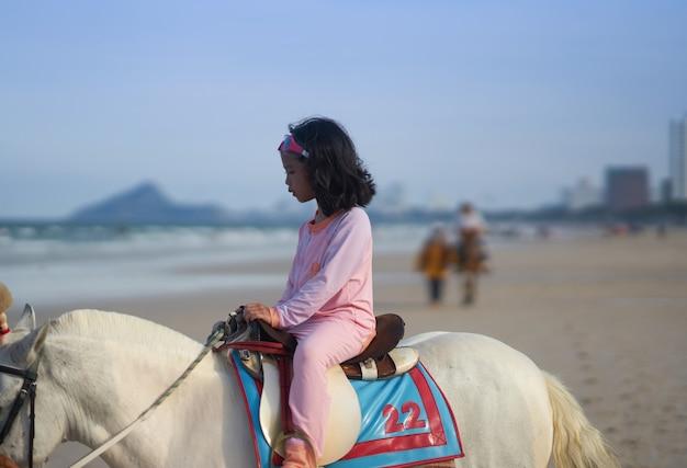 Garota em traje de banho andar a cavalo em frente à praia nas férias de verão