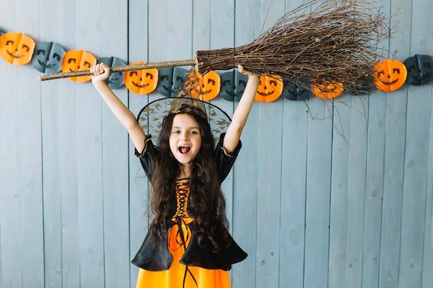 Garota em traje de bruxa segurando a vassoura nas mãos levantadas
