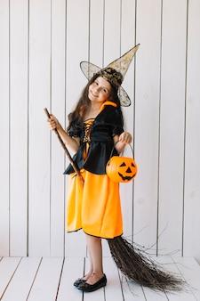Garota em traje de halloween com abóbora cesta e vassoura posando no estúdio